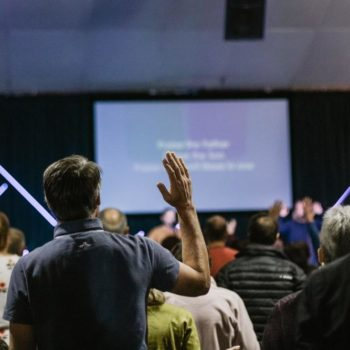 shallow focus photo of person raising right hand